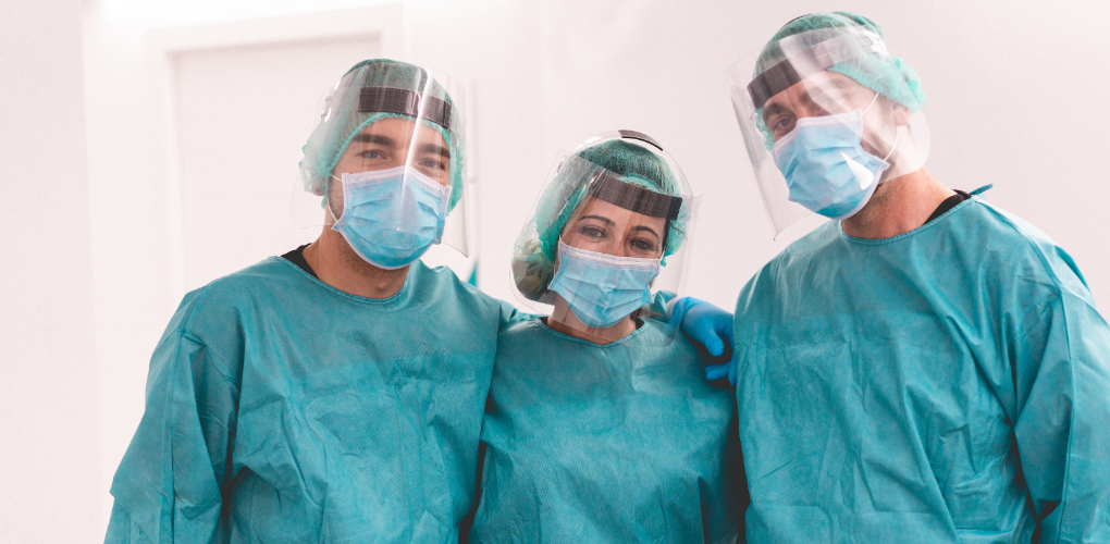 three dentists in PPE stand with their arms around each other
