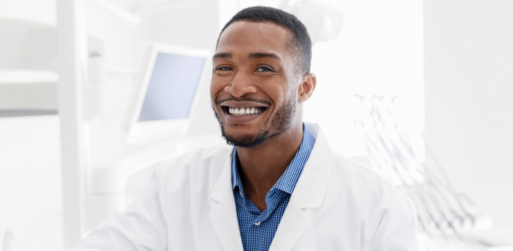 A male dentist smiles on his first day as a dentist.