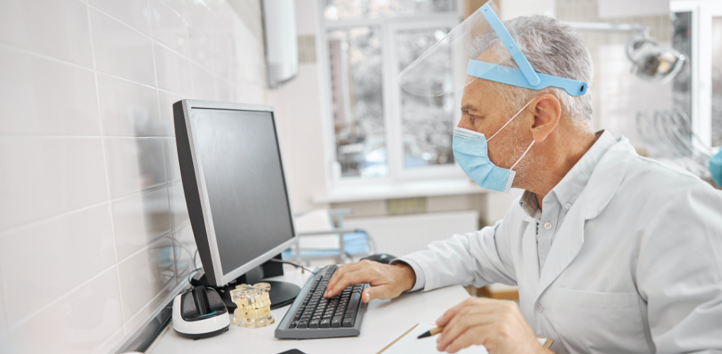 A white male dentist uses a computer at a desk in the office. This blog is about selling a dental practice.